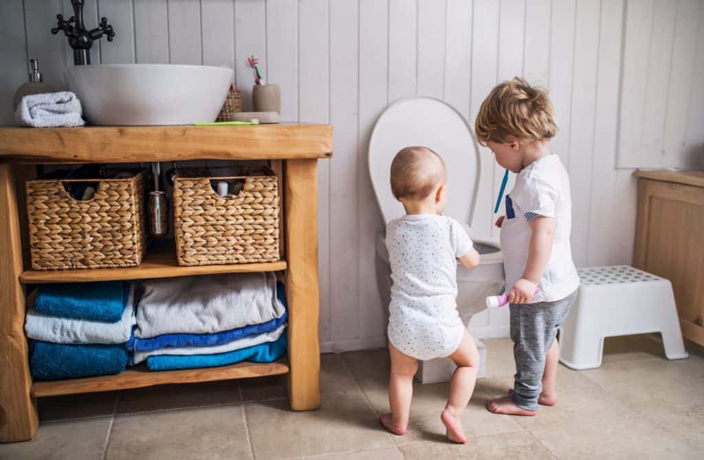 Two toddler children with toothbrush standing by the toilet in the bathroom at home.