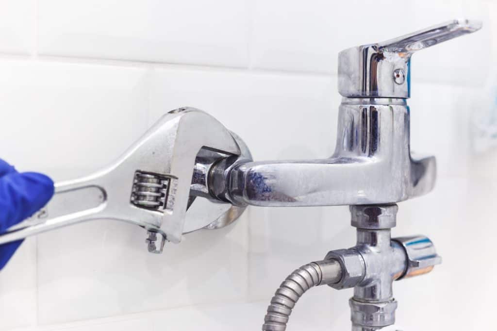 Plumber uses pipe wrench for service shower mixer tap