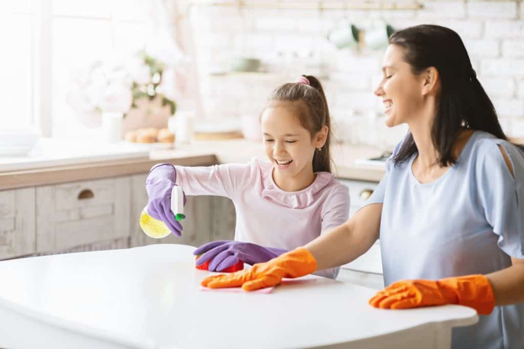 Cheerful mother and daughter cleaning kitchen together