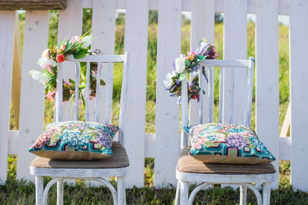 Two vintage white chairs, colorful velvet pillow and fence palisade on background decorated with